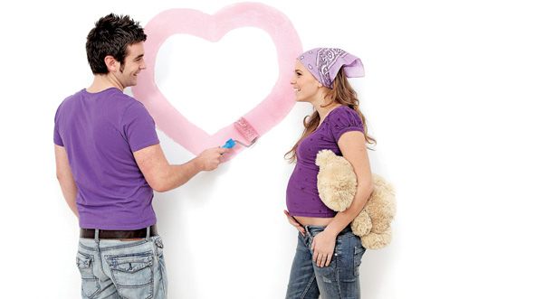Young couple, husband and pregnant wife painting nursery wall.