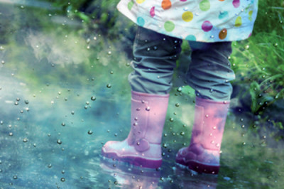 cute little girl is playing in muddy puddles