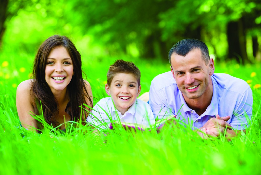 Happy family of three lying on grass while reading book. Concept