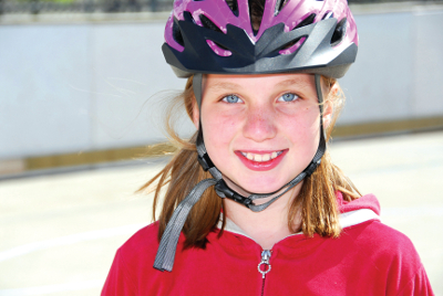 Portrait of a young girl rolleblading in a helmet