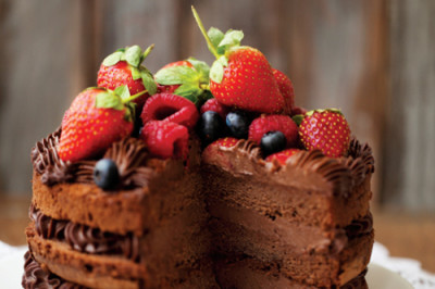 Piece of chocolate cake with icing and fresh berry on wooden background