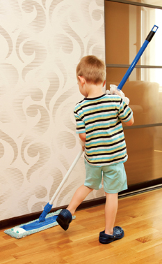 Little boy cleaning apartment, washing floor