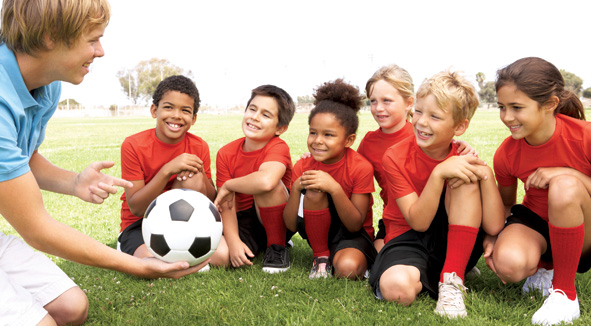 Young Boys And Girls In Football Team  With Coach
